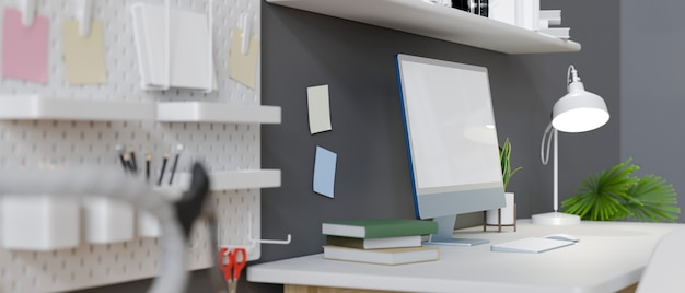 Side view creative and stylish workplace in apartment with computer blank screen mockup grey wall