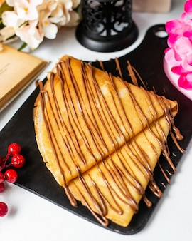 Side view of crepe with chocolate cocoa syrup on a wooden cutting board