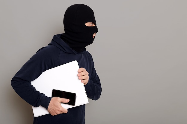 Side view of a criminal guy escaping with a stolen laptop