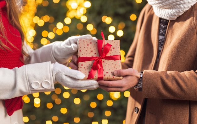 Side view of crop unrecognizable female presenting wrapped gift box with red ribbon to boyfriend during christmas date near festive glowing fir tree