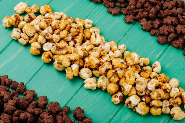 Side view of crunchy chocolate corn flakes and caramel popcorn on green wooden background