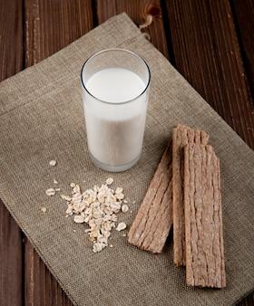 サイドビューカリカリのクリスプブレッドオートミールと木製のテーブルに牛乳のガラス