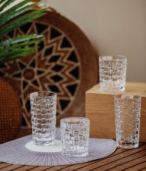 Side view of crystal glasses with embossed pattern on a wooden surface