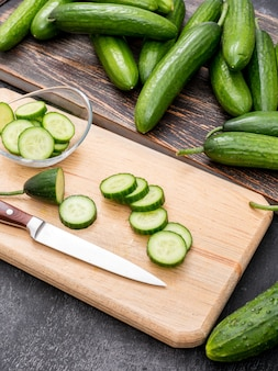 Side view cucumber sliced on wooden cutting board