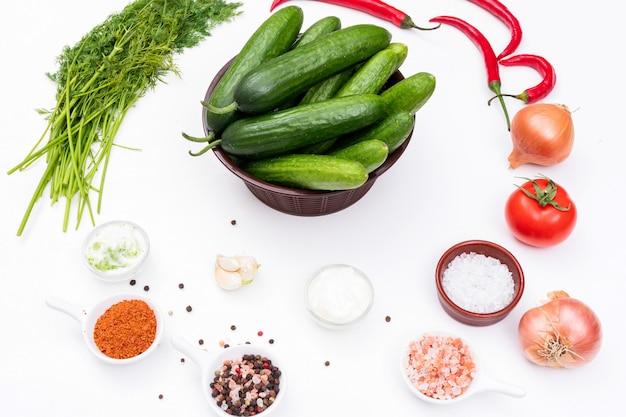Вид сбоку огурец с луком, укропом, томатами и специями