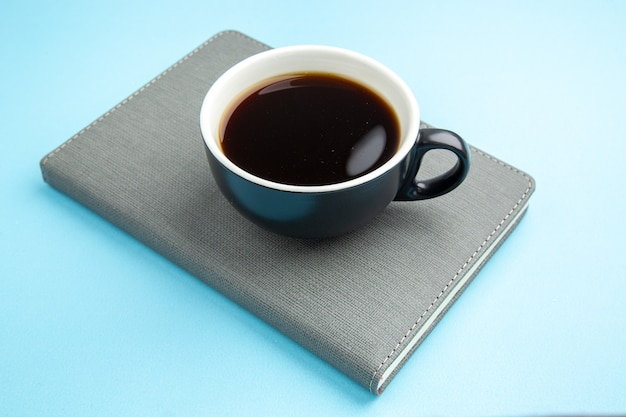 Side view of a cup of black tea on gray notebook on blue surface
