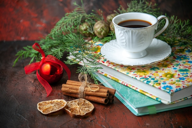 Side view of a cup of black tea on two books cinnamon limes and fir branches decoration accessory on dark background