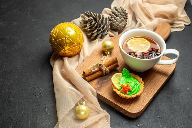 Vista laterale di una tazza di tè nero con accessori per la decorazione del nuovo anno al limone e cannella sul tagliere di legno