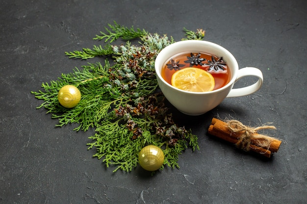 Vista laterale di una tazza di tè nero accessori xsmas e lime alla cannella su sfondo nero