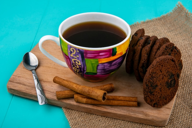 Side view of cup of coffee and cookies with cinnamon and spoon on cutting board on sackcloth and blue background