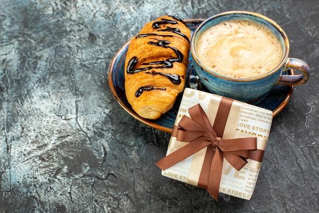 Vista laterale di una tazza di caffè e di un delizioso croissant fresco e di un regalo su una superficie scura