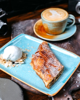 Side view of a cup of coffee latte served with apple strudel with ice cream