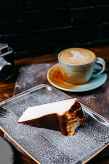 Side view of a cup of coffee latte served with cheesecake