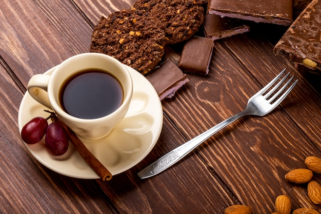 Side view of a cup of coffee with chocolate bar and oatmeal cookies with fork on wooden background