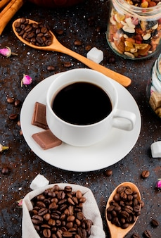 Side view of a cup of coffee with chocolate and a wooden spoon with coffee beans on black background