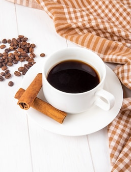Side view of a cup of coffee with cinnamon sticks and coffee beans scattered on white wooden background