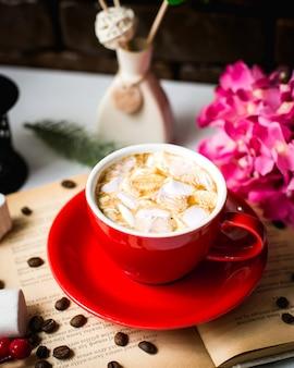 Vista laterale di una tazza di caffè con caramelle gommosa e molle e chicchi di caffè sul tavolo