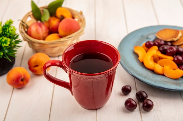 Vista laterale della tazza di caffè con piatto di frittelle e fette di albicocca con ciliegie e cesto di albicocca su sfondo di legno