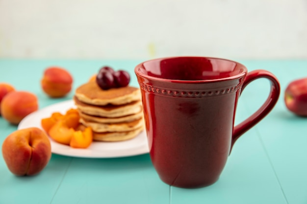 Vista laterale della tazza di caffè con piatto di frittelle e fette di albicocca con ciliegie su superficie blu e sfondo bianco
