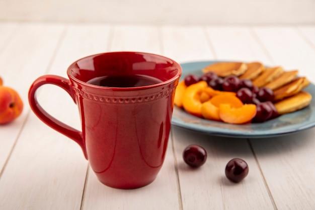 Vista laterale della tazza di caffè con piatto di frittelle e fette di albicocca con ciliegie su fondo di legno