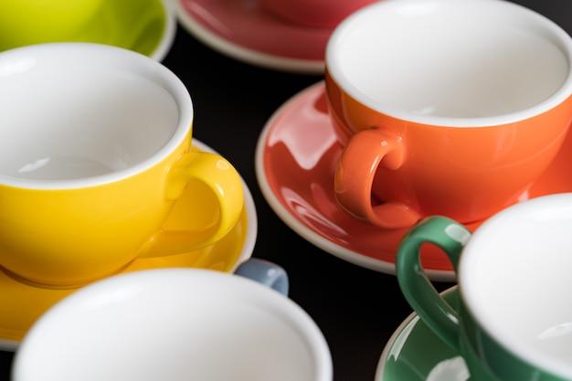 측면에서 볼 수 있는 커피 한 잔은 다채로운 색상이 번갈아 가며 밝고 배경용 접시입니다.