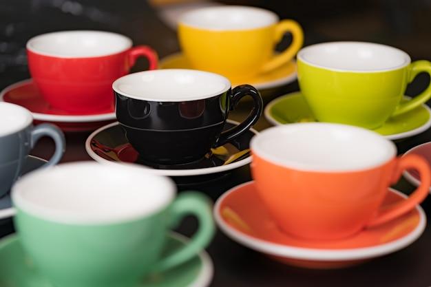 측면에서 볼 수 있는 커피 한 잔은 다채로운 색상을 번갈아 가며 배경을 위한 밝은 redsaucer입니다.