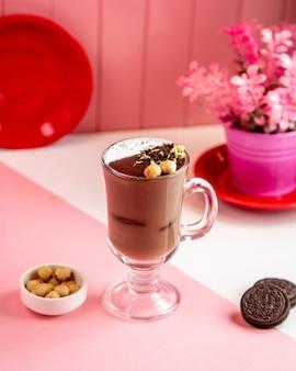 Вид сбоку чашка горячего шоколада с печеньем и орехами