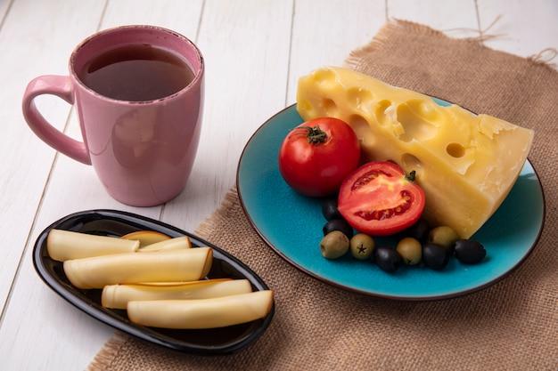 Вид сбоку чашка чая с сырами, томатными маслинами на тарелке и копчеными на белом фоне