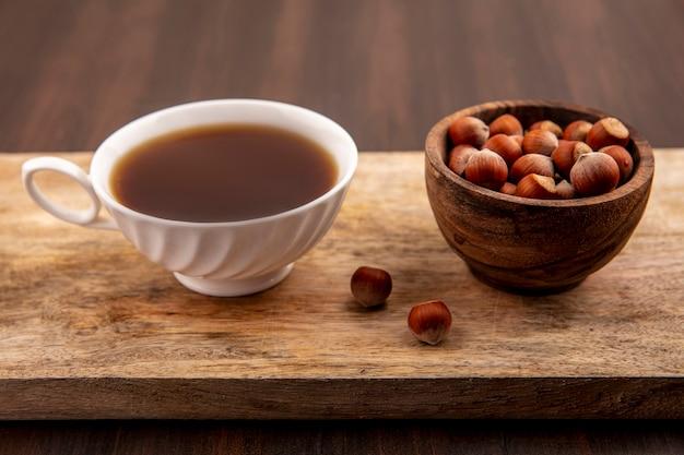 Vista laterale della tazza di tè e ciotola di noci sul tagliere su fondo in legno