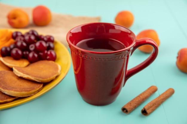 Vista laterale della tazza di tè e cannella e frittelle con ciliegie e fette di albicocca nella piastra e albicocca su sfondo blu