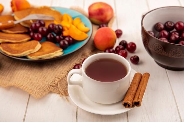 Vista laterale della tazza di tè e cannella sul piattino e frittelle con ciliegie e pezzi di albicocche nel piatto e albicocche ciliegie pera su tela di sacco e ciotola di ciliegie su fondo di legno