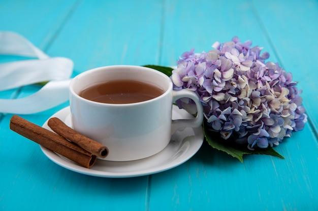 Vista laterale della tazza di tè e cannella sul piattino con fiore e nastro su sfondo blu