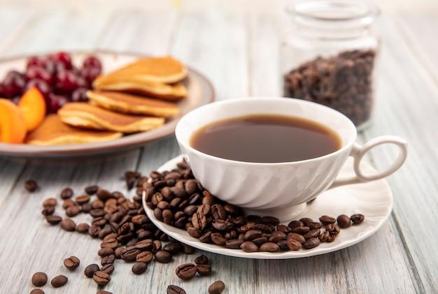 Vista laterale della tazza di tè e caffè in grani sul piattino con piatto di frittelle e ciliegie e fette di albicocca con un barattolo di chicchi di caffè su fondo di legno
