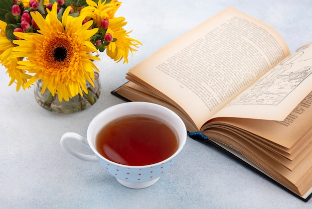 Side view of cup of tea and flowers with open book on white surface