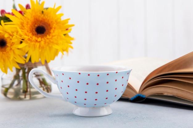 Vista laterale della tazza di tè e fiori con il libro aperto su superficie bianca