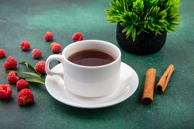 Side view of cup of tea on saucer and cinnamon with raspberries on green surface