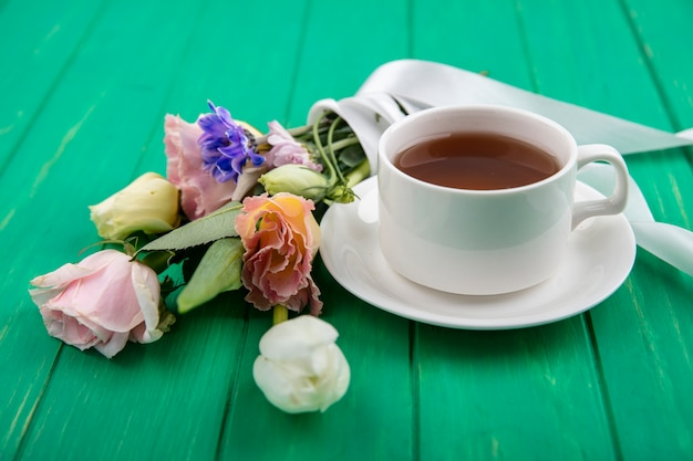 Side view of cup of tea on saucer and flower bouquet on green background