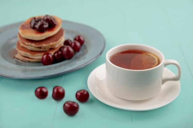 Vista laterale della tazza di tè sul piattino e frittelle con ciliegie nel piatto e su sfondo blu