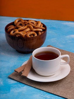 Side view of a cup of tea served with a bowl of bread rings on blue