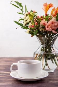 Side view of a cup of tea with beautiful flowers on a glass vase on a wooden table on white wall