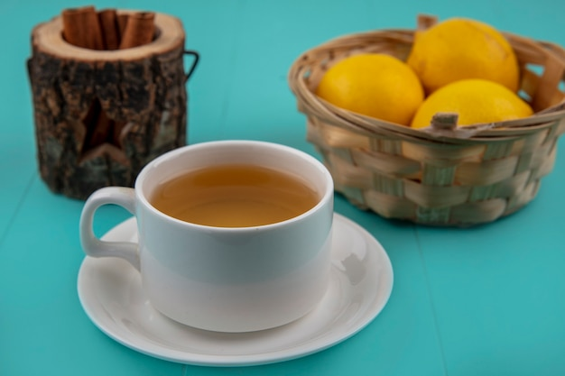 Vista laterale della tazza di tè con una ciotola di cannella e un cesto di limoni su sfondo blu