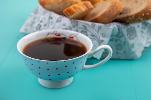 Vista laterale della tazza di tè con pane su sfondo blu