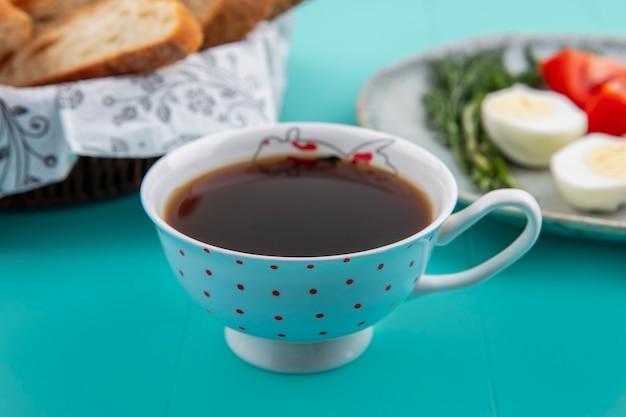Vista laterale della tazza di tè con pane e aneto uovo di pomodoro su sfondo blu