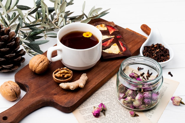 Side view of a cup of tea with chocolate bar with dried fruits and whole walnuts on wood cutting board, dry rose buds in a glass jar and clove spice on white