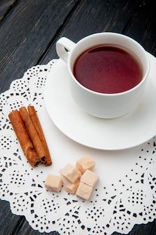 Vista laterale di una tazza di tè con bastoncini di cannella e cubetti di zucchero di canna sul tovagliolo di carta pizzo su fondo di legno scuro