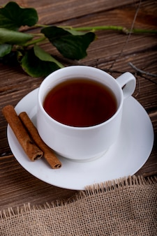 Side view of a cup of tea with cinnamon sticks on a wooden