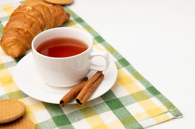 Side view of cup of tea with cinnamon on tea bag and cookies with japanese butter roll on plaid cloth on white background with copy space