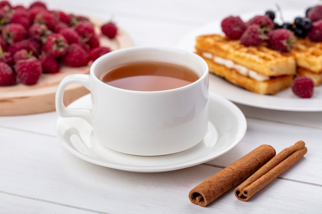 Side view of cup of tea with cinnamon white cherries and sweet waffles with raspberries on a white surface