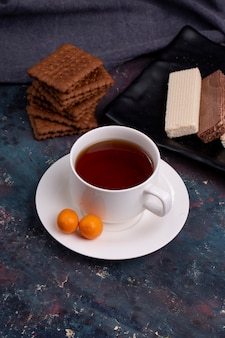 Side view of a cup of tea with cookies on dark