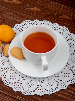 Side view of cup of tea with cookies in teabag and apricots on wooden background